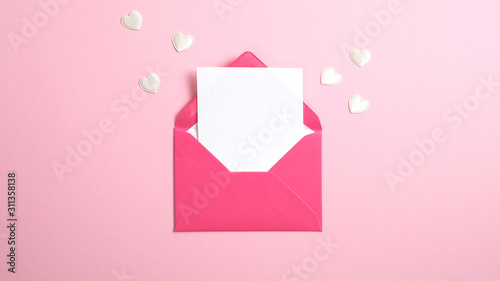 Fototapeta Envelope with blank white paper note inside and Valentine hearts on pink background