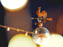 Wind Vane In Shape Of Rooster On Shiny Disco Ball. Red Square Decorated For New Year And Christmas Fair. Moscow, Russia.