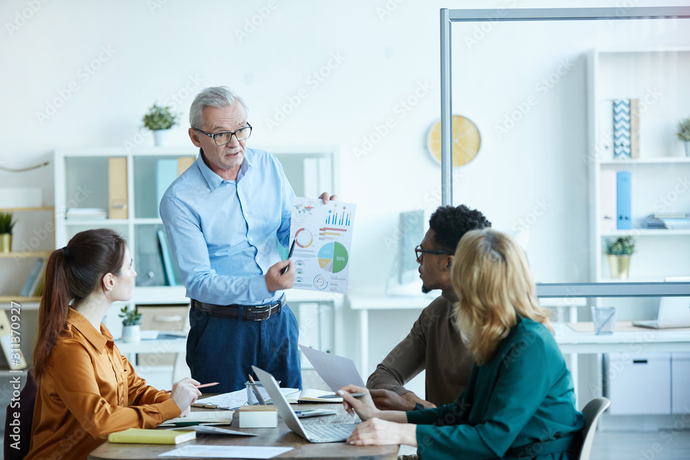 Fototapeta Mature male leader standing and pointing at financial report and explaining it to his colleagues during business meeting