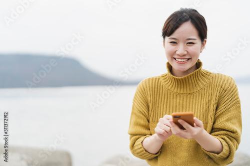 Fotografie, Obraz 海でスマートフォンを使う女性