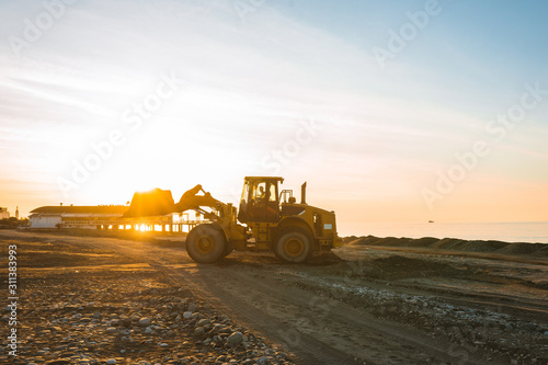 Photo Excavator loads the excavation onto a truck (hydraulic)are heavy construction equipment consisting of an arrow,a bucket and a cabin on a rotating platform