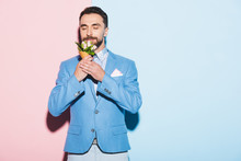 Smiling Man Smelling Bouquet On Pink And Blue Background