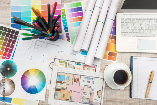 Obraz Close up view of color palette swatch and house building plans on office desk with laptop and cup of coffee for break - fototapety do salonu