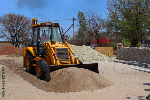 Photo A backhoe pushing a pile of sand
