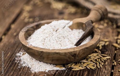 Fototapeta Old wooden table with fresh Oat Flour (close-up shot; selective focus) obraz