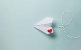 papierowy samolot miłości na kolorowym tle .. Koncepcja wiadomości o miłości. Walentynki. Deklaruj miłość. Miłosna notatka.