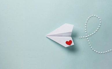 paper love airplane on color background..The concept of a love message. Valentine's Day. Declare love. Love note.