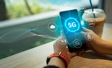 Close Up Of Female Hand Holding A Phone With A 5G Hologram In Coffee Shop. 5G Network Wireless Systems.The Concept Of 5G Network, High-speed Mobile Internet, New Generation Networks.