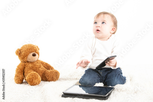 Baby with a mobile in his hand and with a tablet and a teddy bear on the floor #311412307