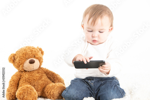 Baby with a mobile in his hand and a teddy bear on the floor #311412352