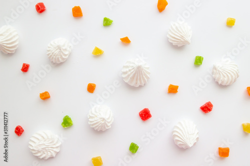 Cuadros en Lienzo  White meringue cookies with colorful candied fruits on white background