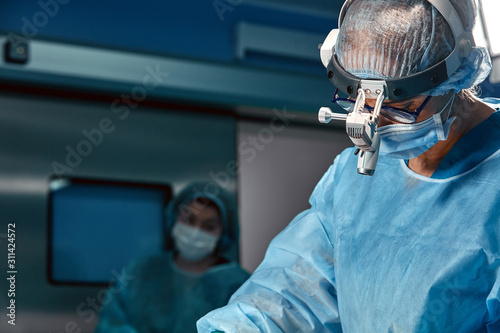 Fotografía Close up portrait of young female surgeon doctor wearing protective mask and hat during the operation