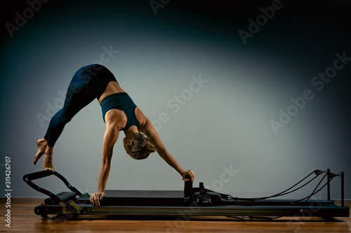 Carta da parati  Young girl doing pilates exercises with a reformer bed