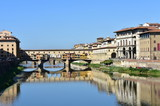 View of Ponte Vecchio with blue sky and water reflections from bridge over the Arno River. Florence, Italy.