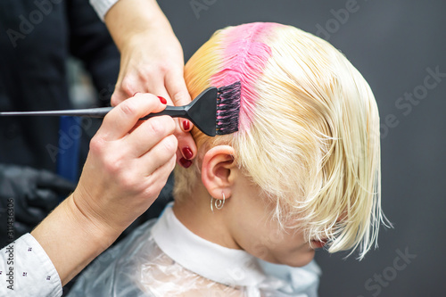 Hands of hairdresser dyes your hair pink, close up pink coloring.