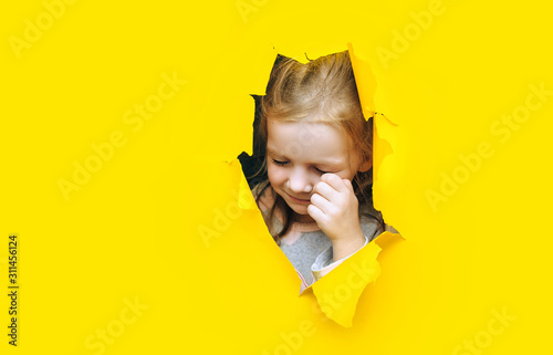 Fototapeta The little red-haired funny girl screams and cry desperately from fear and fright, peering out from yellow paper in the center