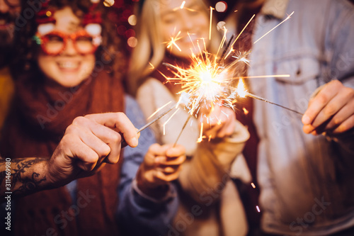 Obraz Close view of sparklers. Group of happy friends celebrating New Year with sparklers. New year party. - fototapety do salonu