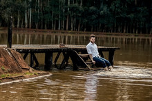 Boy In White Social Shirt Sitting On A Deck Over The Pond.