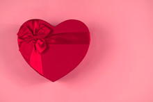 Red Gift Box Heart Shape With Red Ribbon On A Pastel Pink Background, Gift Concept Valentine Day, Top Wiev, Copy Space