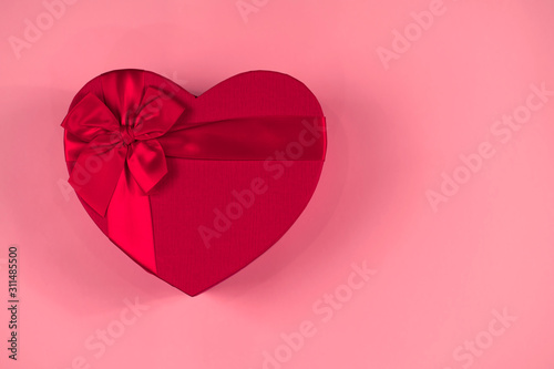 Fotografie, Tablou Red gift box heart shape with red ribbon on a pastel pink background, gift conce