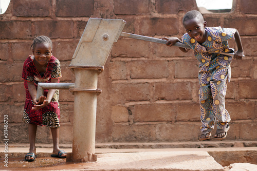 Photographie Happy Little African Boy Pumping Water For His Sister
