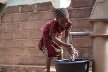 Small African Girl Washing Her...
