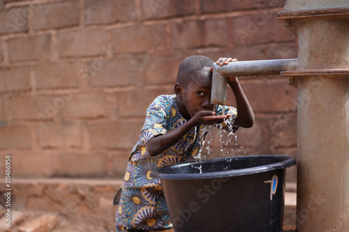 Obraz na plátně Little African Boy At The Community Borehole Quenching His Thirst