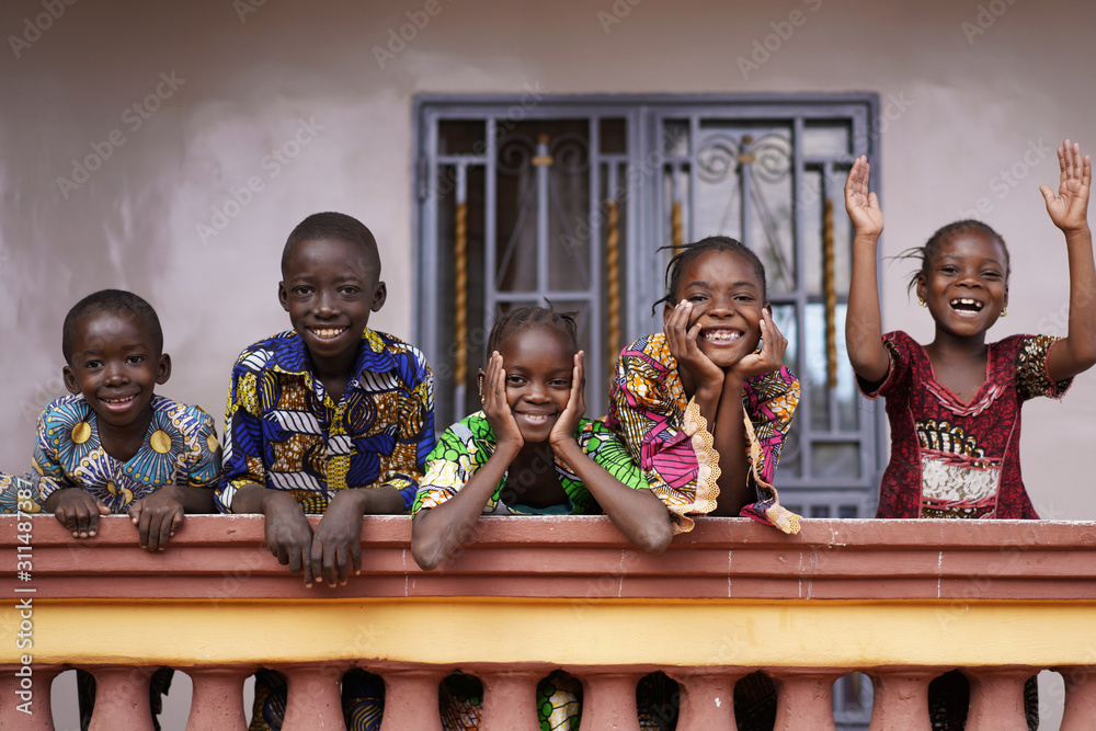 Fototapeta Five African Children Greeting Bypassers From A Colonial House Balcony