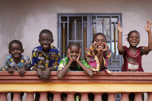 Five African Children Greeting Bypassers From A Colonial House Balcony