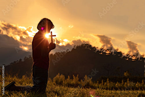 Leinwand Poster Silhouette of woman praying with cross in nature sunrise background, Crucifix, Symbol of Faith
