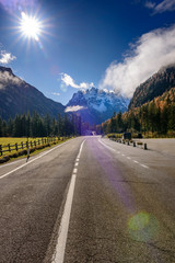 Asphalt roads in the Italian Alps in South Tyrol, during autumn season / Sunny autumn day with dolomite mountains in background / Heavy sun flare thought the frame