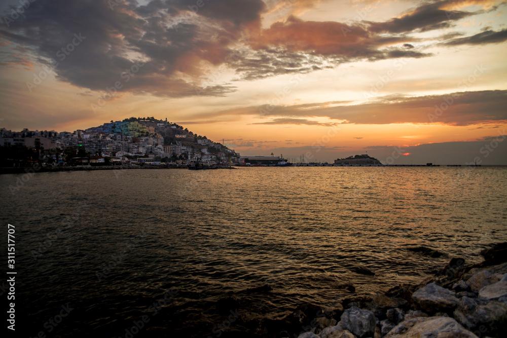 Kusadasi, Turkey - September 17, 2019: View of the coast of Kusadasi, Turkey. Sunset over the port in the tourist town.