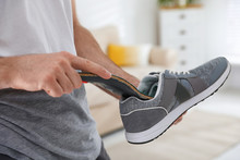 Man Putting Orthopedic Insole Into Shoe At Home, Closeup