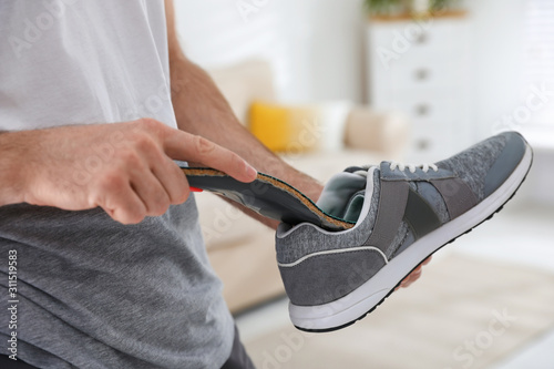 Man putting orthopedic insole into shoe at home, closeup Canvas Print