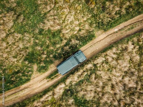 Off-Road Abenteuer mit SUV Geländewagen auf Feldweg von oben фототапет