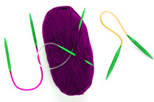 Purple Yarn Skein For Hand Knitting And Crochet On White Background Isolated. Ball Of Bright Violet Wool With Green Needles. Trendy Hat Knitting Process. Hank Of Colorful Thread For Handmade Craft