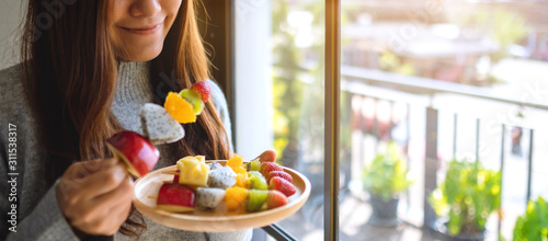 Closeup image of an asian woman holding and eating a fresh mixed fruits on skewers