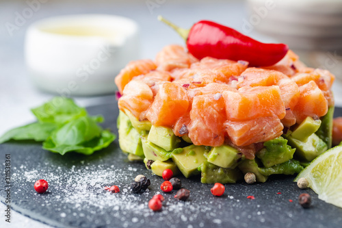 Fotografia Delicious avocado and raw salmon salad, tartare, served on a black plate with li