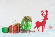 Beautiful Christmas Holiday And New Year Greeting Card. Red Deer Carring A Sled With Various Gift Boxes On The Fresh Snow Background