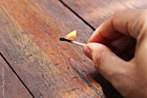 Photo A man holding a lit match