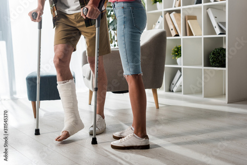 Tela cropped view of woman standing near man holding crutches at home