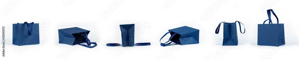 Fototapeta Banner from empty gift paper bags, shopping bag in classic blue color isolated on white background. Mockup of blank craft package. Concept for presents holidays.