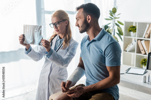 Fotografía attractive orthopedist in glasses holding x-ray near handsome injured man