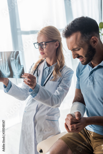 Fotomural attractive orthopedist in glasses holding x-ray near injured man suffering from