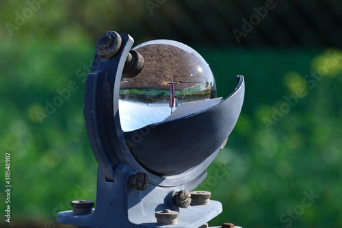 Foto Weather station and the sun in a blue sky reflected in the glass sphere of a bea