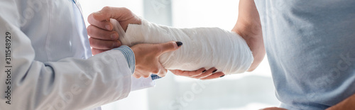 mata magnetyczna panoramic shot of orthopedist touching injured hand of man