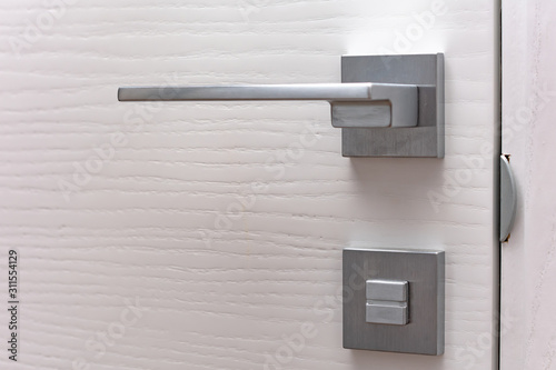 Obraz Modern chrome door handle and lock on white wooden door. Close-up elements of the modern interior of the apartment. Ajar white door. - fototapety do salonu