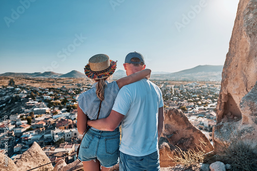 Young couple of travelers on a hill with stunning views of Goreme city in Cappad Canvas Print