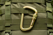 Steel Climbing Carabiner Attached To A Green Military Tactical Backpack
