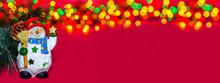 Holiday Greeting Banner. Toy Christmas Snowman With Star On Red Background. Composition Of Christmas Tree, Berries, Apple And Colorful Bokeh Lights Garland. Classic Atmosphere Of New Year. Copy Space